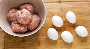 Picture of hard-boiled eggs and sausage balls that will be wrapped around eggs to make paleo scotch eggs