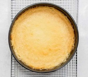 finished cheesecake with tin foil removed and cooling on cooling rack