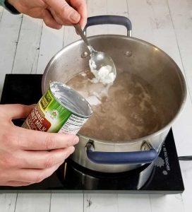 adding coconut cream to soup